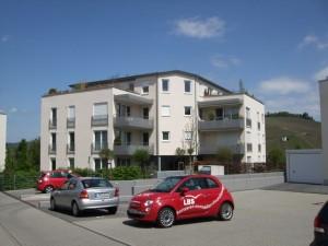 Parkplatz mit Autos, Wohnhaus im Hintergrund